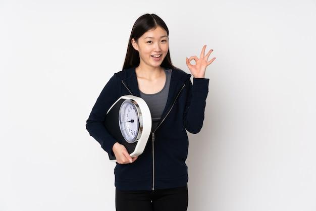Jeune femme asiatique isolée sur un espace blanc tenant une machine de pesage et faisant signe ok