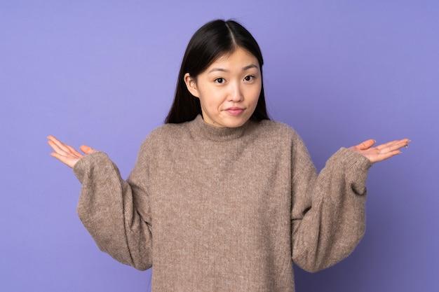 Jeune femme asiatique isolée sur l'espace violet ayant des doutes tout en levant les mains