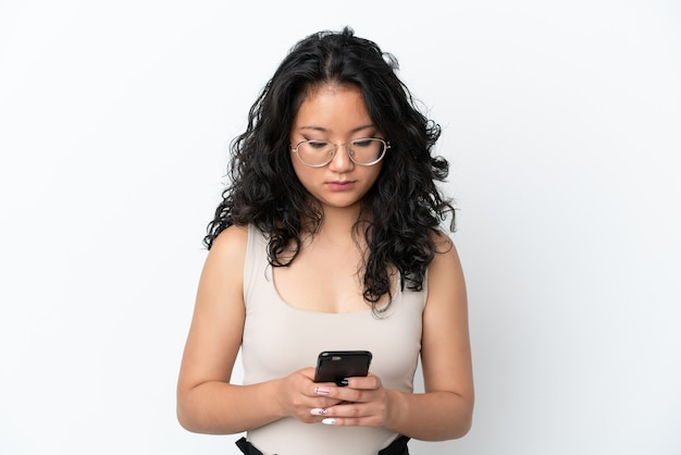 Jeune femme asiatique isolée sur fond blanc à l'aide de téléphone portable