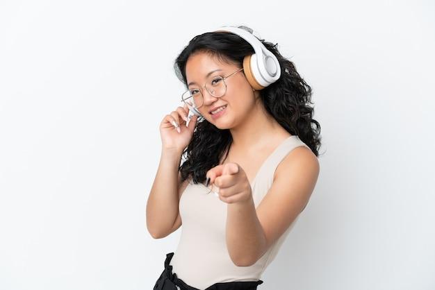 Jeune femme asiatique isolée sur fond blanc, écoutant de la musique et pointant vers l'avant