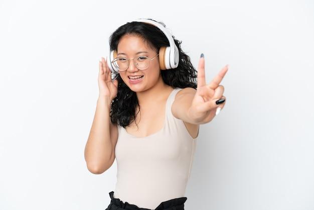 Jeune femme asiatique isolée sur fond blanc, écouter de la musique et chanter