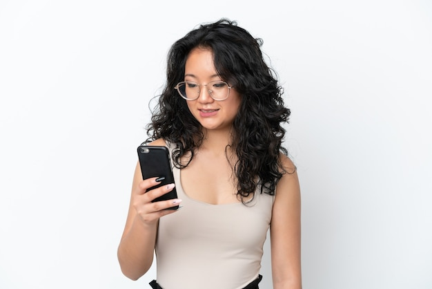 Jeune femme asiatique isolée sur fond blanc envoyant un message ou un e-mail avec le mobile