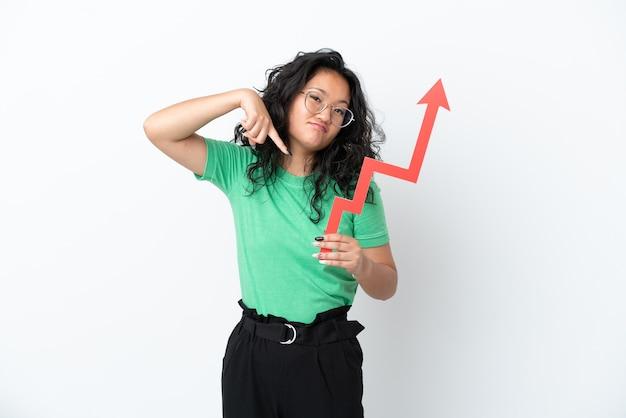 Jeune femme asiatique isolée sur fond blanc tenant une flèche montante et la pointant