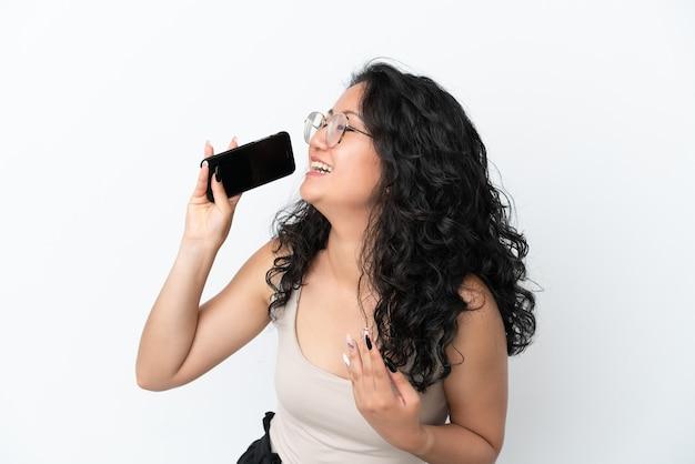 Jeune femme asiatique isolée sur fond blanc utilisant un téléphone portable et chantant