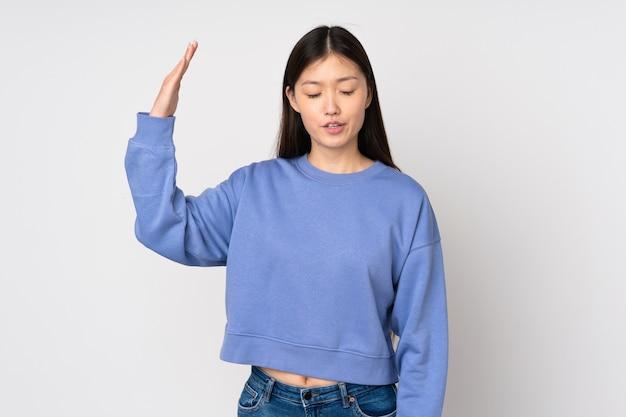 Jeune femme asiatique isolée sur fond avec une expression fatiguée et malade