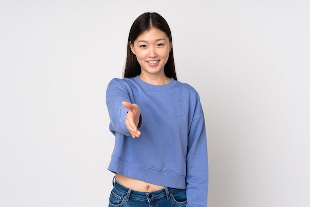 Jeune femme asiatique isolée sur fond se serrant la main pour conclure une bonne affaire