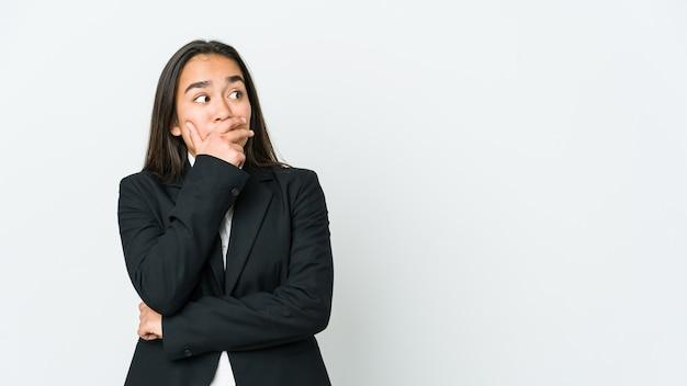 Jeune femme asiatique isolée sur un mur blanc réfléchie à la recherche d'un espace de copie couvrant la bouche avec la main.