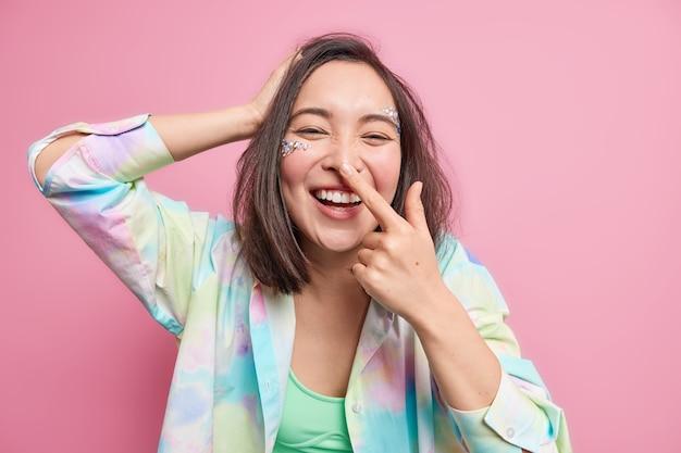 Une jeune femme asiatique joyeuse s'amuse des sourires touche largement le nez exprime des émotions positives a le visage décoré de petites pierres porte une chemise colorée isolée sur un mur rose. expressions faciales