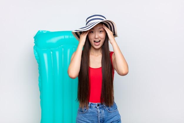 Jeune femme asiatique levant les mains à la tête, bouche bée, se sentant extrêmement chanceuse, surprise, excitée et heureuse. concept d'été