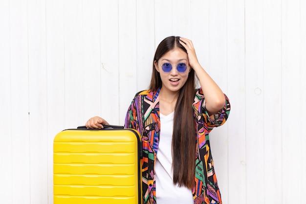 Jeune femme asiatique levant les mains à la tête, bouche bée, se sentant extrêmement chanceuse, surprise, excitée et heureuse. concept de vacances