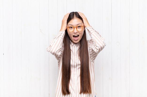 Jeune femme asiatique levant les mains à la tête, bouche bée, se sentant extrêmement chanceux, surpris, excité et heureux