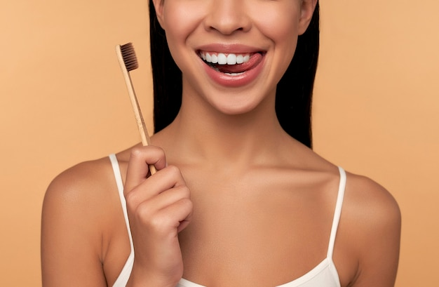 Jeune femme asiatique en lingerie blanche avec une brosse à dents et des dents blanches sur beige. concept d'hygiène dentaire