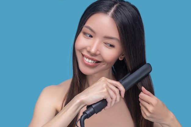 Jeune femme asiatique lissage des cheveux et se sentir heureux
