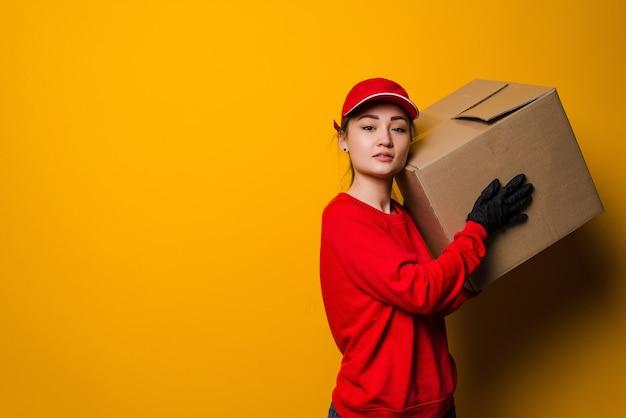 Jeune femme asiatique de livraison tenant et portant une boîte en carton isolée. service de livraison, quarantaine, coronavirus