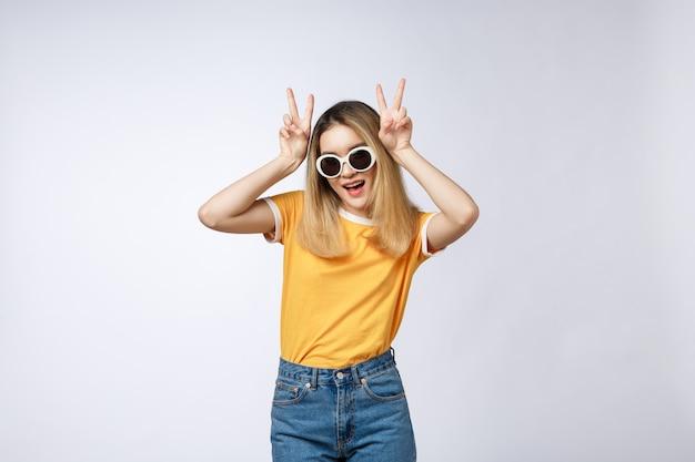 Jeune femme asiatique, lunettes de soleil montrant et pointant vers le haut avec les doigts