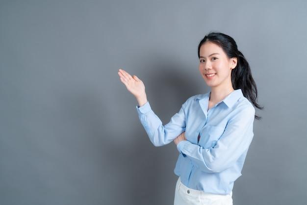 Jeune femme asiatique avec la main présentant sur le côté