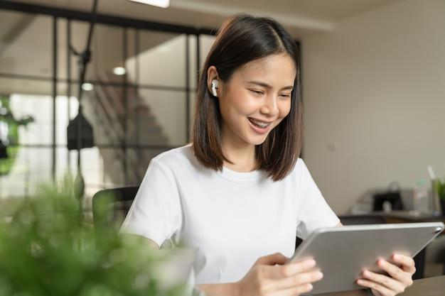 Jeune femme asiatique main tenant une tablette numérique à la maison.