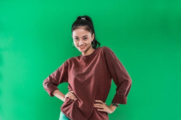 Jeune femme asiatique avec les mains sur les hanches tandis que l'expression sourit sur le visage dans un mur vert