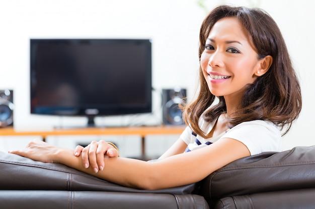 Jeune femme asiatique à la maison sur le canapé