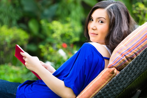 Jeune femme asiatique à la maison dans le jardin