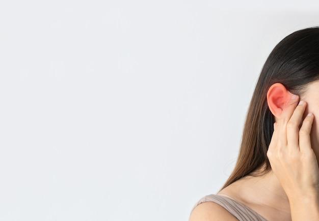 Jeune femme asiatique a mal à l'oreille, souffrant d'otite sur fond blanc avec accent rouge, espace libre, gros plan