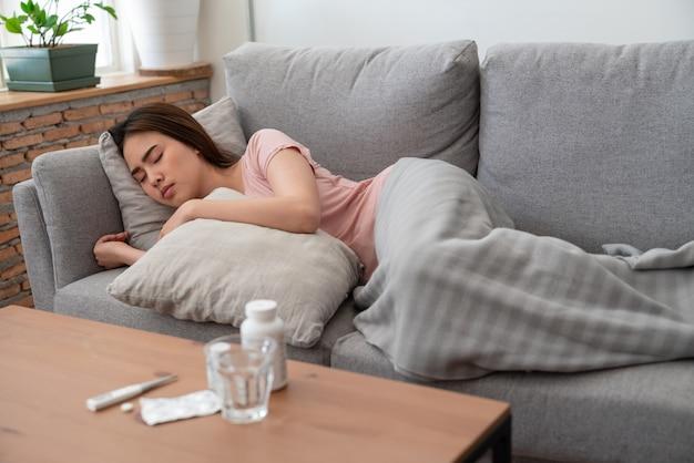 Jeune femme asiatique malade relaxant et dormir sur le canapé avec oreiller après avoir pris des médicaments avec un verre d'eau