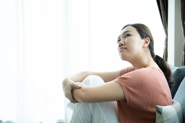 Jeune femme asiatique malheureuse ayant un problème de trouble dépressif et vivant seule dans le salon. concept de soins de santé mentale chez les jeunes.
