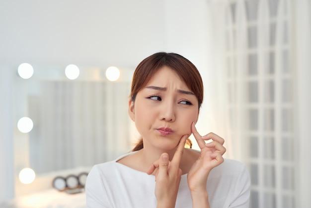 Jeune femme asiatique malheureuse toucher sa peau