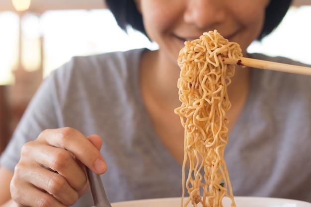 Jeune femme asiatique mange des nouilles, une femme prend son petit déjeuner