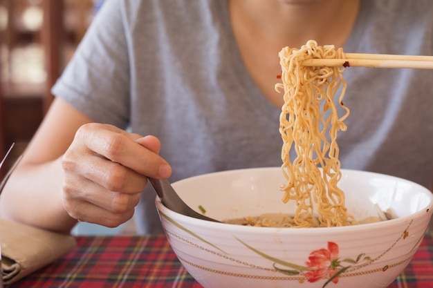 Une jeune femme asiatique mange des nouilles, une femme prend son petit déjeuner.