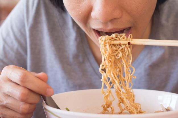 Jeune femme asiatique mange des nouilles