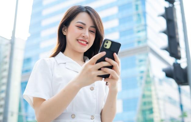 Jeune femme asiatique marchant et à l'aide de smartphone dans la rue