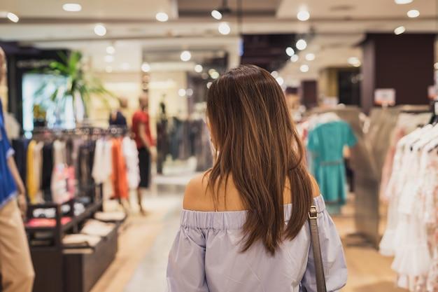 Jeune femme asiatique, marchant dans le magasin de vêtements au centre commercial