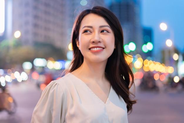 Jeune femme asiatique marchant dans la rue pendant la nuit