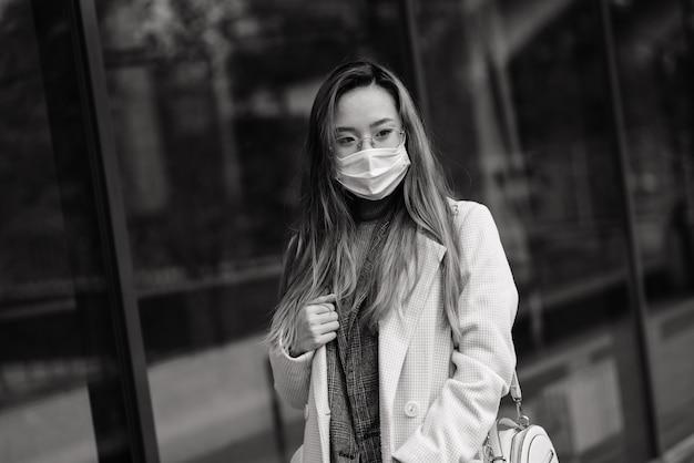 Jeune femme asiatique avec masque chirurgical protection faciale. elle fait la navette entre la maison et le lieu de travail en ville