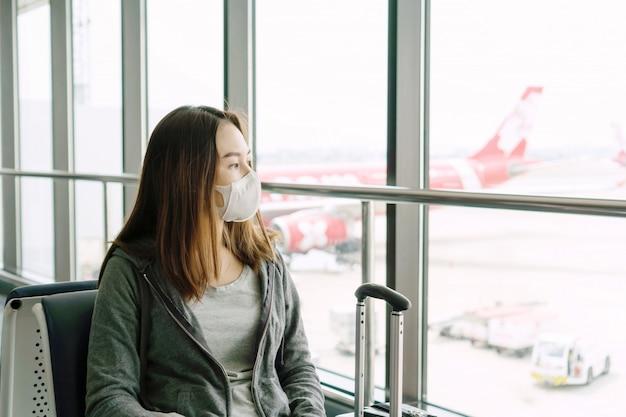 Jeune femme asiatique avec masque facial chirurgical protection assis au terminal de l'aéroport. protection coronavirus / covid-19 et pollution de l'air concept pm2.5.