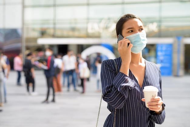 Jeune femme asiatique avec masque parlant au téléphone tout en prenant un café sur le pouce comme la nouvelle norme dans la ville en plein air