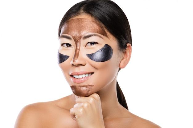 Jeune femme asiatique avec un masque peel-off purifiant sur son visage
