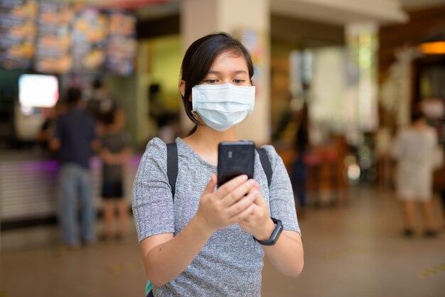 Jeune femme asiatique avec masque de protection contre l'épidémie de virus corona à l'aide de téléphone à l'intérieur du restaurant