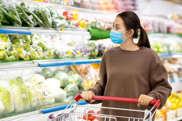 Jeune femme asiatique avec masque de protection poussant le panier pour acheter des légumes frais dans un supermarché pendant l'épidémie de virus covid-19.