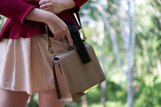 Jeune femme asiatique mettant une arme à feu dans son sac à main