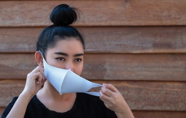 Jeune femme asiatique mettant un masque médical