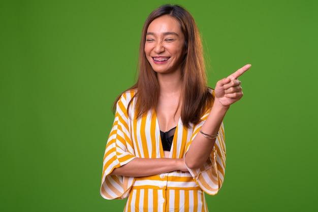 Jeune femme asiatique mince sur fond vert