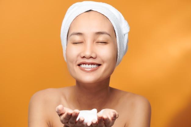 Jeune femme asiatique montrant un nettoyant moussant sur sa main tout en portant une serviette de bain sur fond orange.