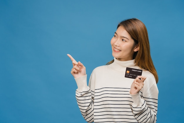 Une jeune femme asiatique montre une carte bancaire de crédit avec une expression positive, sourit largement, vêtue de vêtements décontractés se sentant heureuse et se tient isolée sur un mur bleu