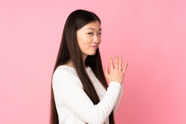 Jeune femme asiatique sur mur isolé complotant quelque chose