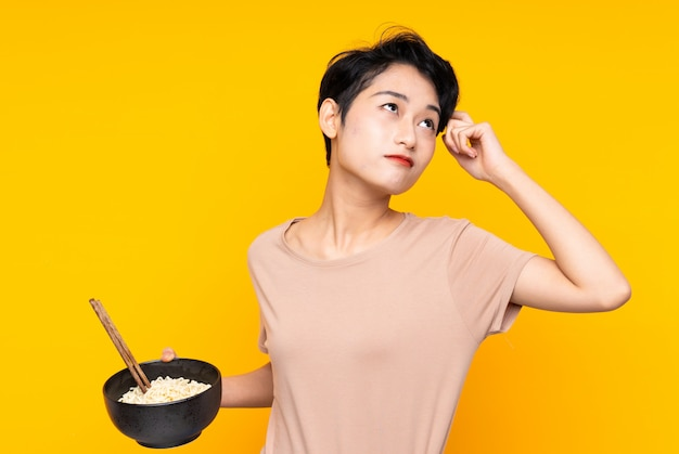 Jeune femme asiatique sur mur jaune isolé ayant des doutes et avec une expression de visage confuse tout en tenant un bol de nouilles avec des baguettes