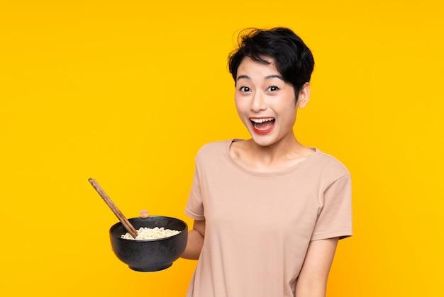 Jeune femme asiatique sur mur jaune isolé avec surprise et expression faciale choquée tout en tenant un bol de nouilles avec des baguettes