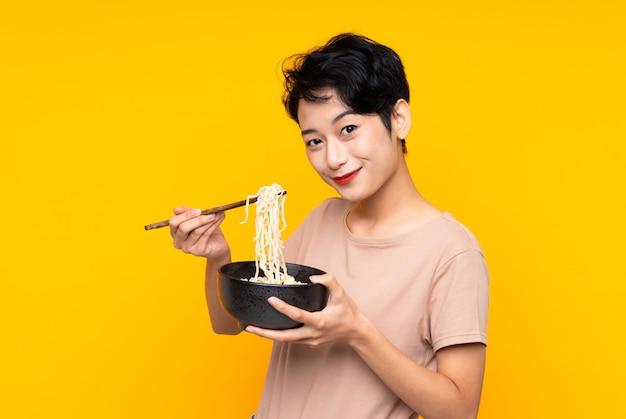 Jeune femme asiatique sur mur jaune isolé tenant un bol de nouilles avec des baguettes