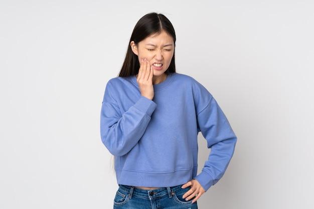 Jeune femme asiatique sur mur avec mal aux dents